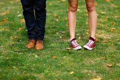 Fille dans des espadrilles rouges et un homme dans des chaussures brunes Image libre de droits