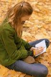 Fille dans des feuilles d'automne avec un carnet photos libres de droits