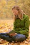 Fille dans des feuilles d'automne avec un carnet photo stock