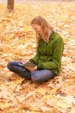 Fille dans des feuilles d'automne avec un carnet image libre de droits
