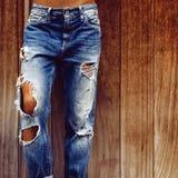 Fille dans des jeans déchirés élégants sur le fond en bois images stock