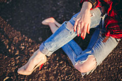 Fille dans des jeans déchirés se reposant sur la route Photographie stock