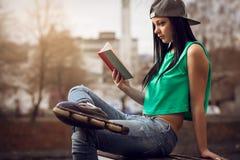 Fille dans des jeans lisant un livre sur le banc Image stock