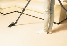 Fille dans des jeans nettoyant à l'aspirateur la maison Tapis lumineux Photographie stock libre de droits