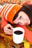 Fille dans des lames d'orange d'automne avec le coffe de cuvette. Photographie stock libre de droits