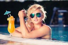 Fille dans des lunettes de soleil avec le jus d'orange frais Photos stock