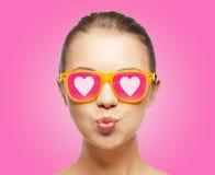 Fille dans des lunettes de soleil roses soufflant le baiser Photos stock