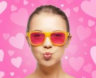 Fille dans des lunettes de soleil roses soufflant le baiser Image stock
