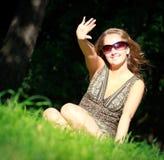 Fille dans des lunettes de soleil se reposant dans l'herbe Image libre de droits