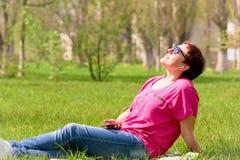 Fille dans des lunettes de soleil sur l'herbe verte Image libre de droits