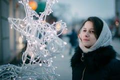 Fille dans des mitaines sur la rue à Noël Fond de Noël Mode de vie de concept, hiver, vacances, Noël heureux, nouvelle année photographie stock libre de droits