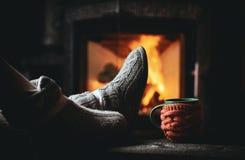Fille dans des pantoufles, tasse, sur la cheminée proche en bois de vintage Images libres de droits