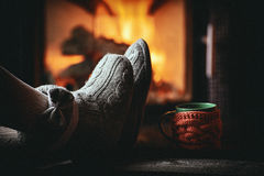 Fille dans des pantoufles, tasse, sur la cheminée proche en bois de vintage Photographie stock