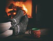 Fille dans des pantoufles, tasse, sur la cheminée proche en bois de vintage Photo libre de droits