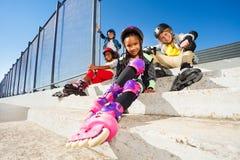Fille dans des patins de rouleau se reposant avec des amis Image stock
