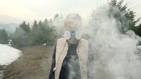 Fille dans des regards de masque de gaz directement par la fumée banque de vidéos