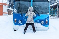 Fille dans des supports d'un manteau de fourrure beige et de capot avec le sien de retour devant l'autobus de chariot photos libres de droits
