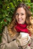 Fille dans des vêtements chauds sur le parc d'automne tenant une tasse avec le thé chaud Image libre de droits