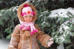 Fille dans des vêtements de l'hiver à un pin snow-covered Photos libres de droits