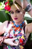 Fille dans des vêtements ethniques dans le jardin tropical avec le serpent Photographie stock libre de droits