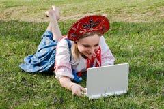 Fille dans des vêtements nationaux avec un ordinateur portatif sur l'herbe Photo stock