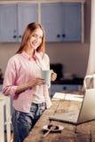 Fille dans des vêtements sport tenant la tasse, se tenant à la maison dans la cuisine Photographie stock