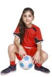 Fille dans l'équipement complet du football se reposant sur un football photographie stock libre de droits