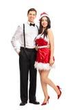 Fille dans l'équipement de Santa posant avec son ami Image stock
