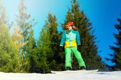 Fille dans l'équitation de masque de ski sur le surf des neiges Photographie stock libre de droits