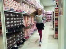 Fille dans l'affichage de boutique de chaussure Photographie stock libre de droits