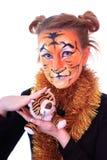 Fille dans l'apparence un tigre avec un animal de tigre de jouet. Photographie stock libre de droits