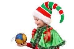 Fille dans l'elfe de Santa de procès avec une bille de Noël. Image libre de droits