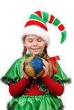 Fille dans l'elfe de Santa de procès avec une bille de Noël. Photographie stock