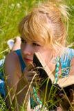 Fille dans l'herbe avec le livre Photographie stock