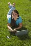 Fille dans l'herbe s'affichant heureusement Photo libre de droits