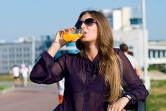 Fille dans l'orangeade de boissons en verre foncés photo stock