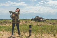 Fille dans l'uniforme militaire et des jeans avec un bazooka dans des ses mains Photo libre de droits