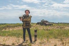 Fille dans l'uniforme militaire et des jeans avec un bazooka dans des ses mains Image libre de droits