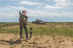 Fille dans l'uniforme militaire et des jeans avec un bazooka dans des ses mains Photo stock