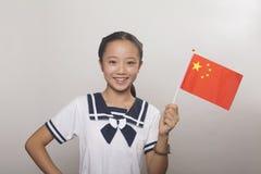 Fille dans l'uniforme scolaire avec le drapeau chinois, tir de studio Photographie stock