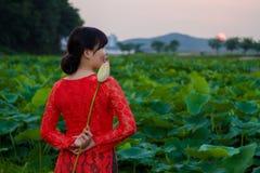 Fille dans la belle robe au lac de lotus Image stock