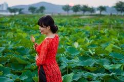 Fille dans la belle robe au lac de lotus Photo stock