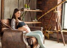 Fille dans la caresse enceinte d'amour, bébé de attente Photographie stock libre de droits