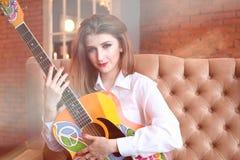 Fille dans la chemise blanche posant avec une guitare dans le style hippie Photographie stock