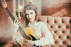 Fille dans la chemise blanche posant avec une guitare dans le style hippie photo stock