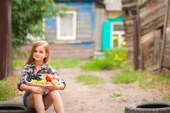 Fille dans la chemise et shorts avec un panier de fruit Agriculteur de fille avec des pommes et des raisins Concept de nourriture photo libre de droits