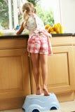 Fille dans la cuisine aidant avec laver vers le haut photo libre de droits