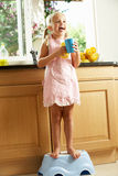 Fille dans la cuisine aidant avec laver vers le haut photographie stock libre de droits