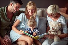 Fille dans la famille regardant le livre d'images image libre de droits
