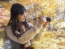 Fille dans la feuille d'automne du Japon avec l'appareil-photo Photographie stock libre de droits